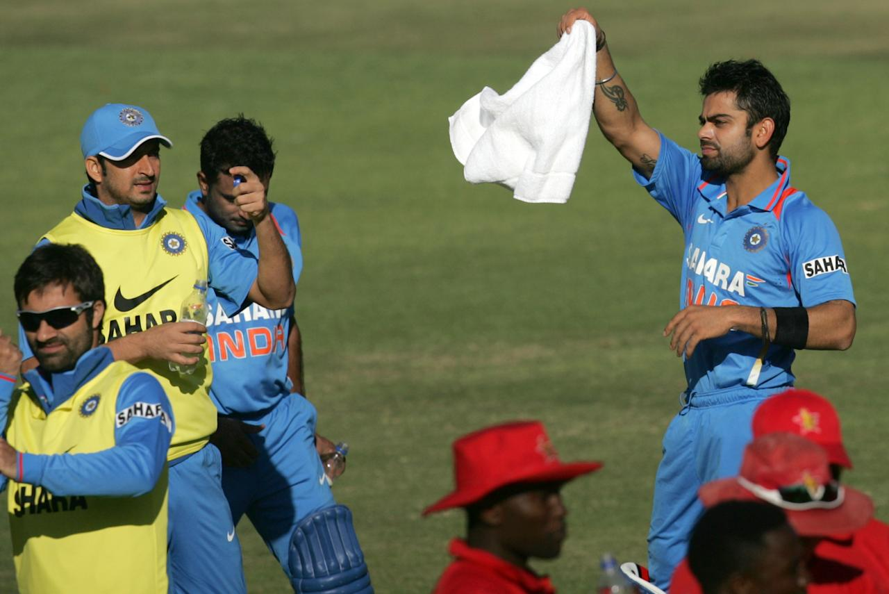 Relentless Indian captain Virat Kohli (R) waves a white towel towards the change room during the first match of the five ODI cricket series between India and Zimbabwe at the Harare Sports Club on July 24, 2013.   AFP PHOTO / Jekesai Njikizana        (Photo credit should read JEKESAI NJIKIZANA/AFP/Getty Images)