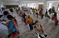 People sit in a waiting area to receive a dose of COVISHIELD, a coronavirus disease (COVID-19) vaccine, in Ahmedabad