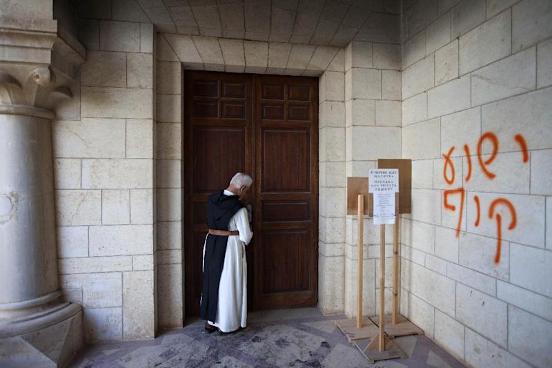"A catholic priest stands at  a door to the Latrun Trappist Monastery where Israeli police say vandals overnight have spray-painted anti-Christian and pro-settler graffiti and set the monastery's door on fire, in Latrun, between Jerusalem and Tel Aviv, Israel, Tuesday, Sept 4, 2012. Suspicion fell on Jewish settlers and their supporters who retaliate against anti-settlement measures, generally by attacking Palestinian property, but also by vandalizing Christian sites and Israeli military facilities. Earlier this week, the government ordered settlers out of two unauthorized enclaves in the West Bank. The Hebrew graffiti  reads, ""Jesus is a monkey.""  (AP Photo/Oded Balilty)"