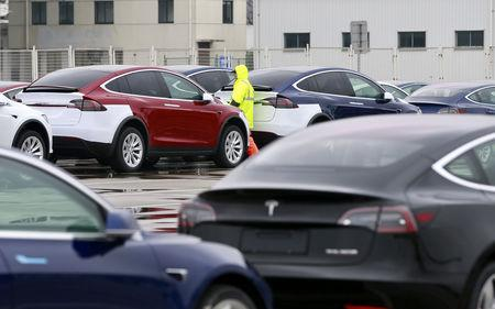 A worker walks next to Tesla cars at a port in Shanghai, China February 22, 2019. REUTERS/Stringer