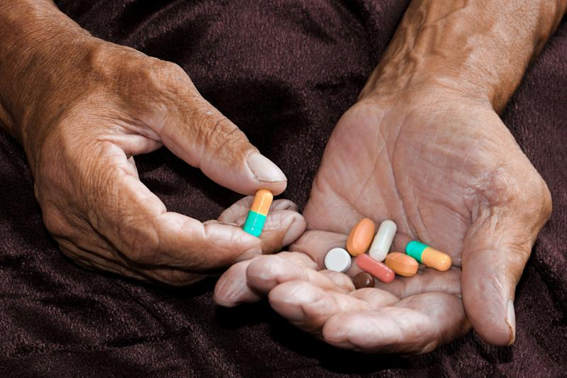 An elderly man holds a lot of colored pills in old hands. Painful old age. Health care of older people. Top View