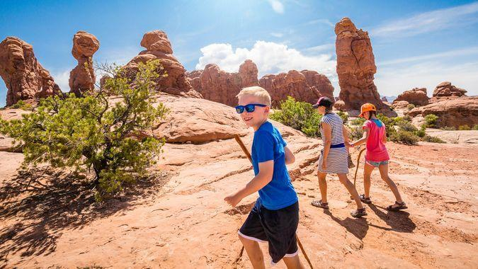 happy family hiking together in the beautiful rock formations of Arches National Park.