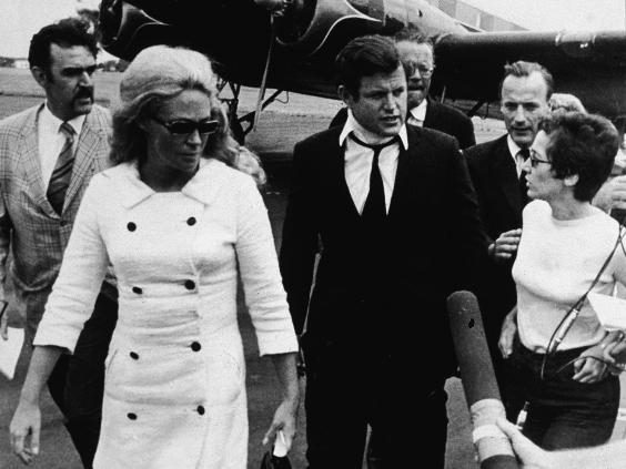 Kennedy, wearing a neck brace, and his wife Joan return from Kopechne's funeral (Getty)