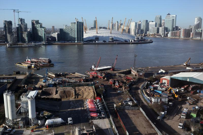 Construction work near the River Thames on the Greenwich Peninsula is seen next to the O2 and Canary Wharf financial district in London