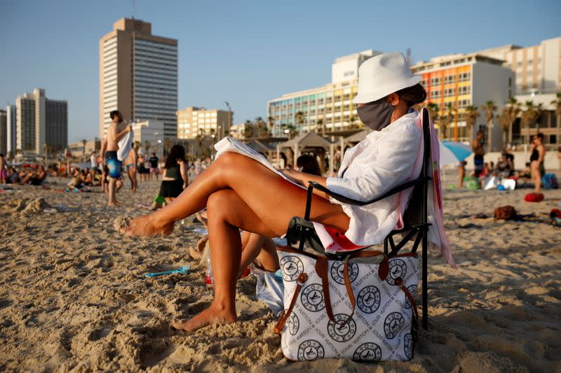 FILE PHOTO: A woman wears a face mask as she sits by the Mediterranean Sea in Tel Aviv as coronavirus disease (COVID-19) restrictions were eased in Israel