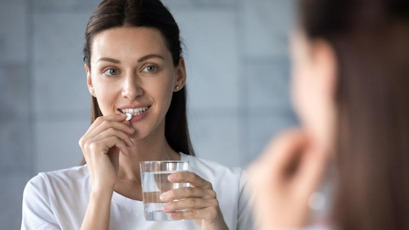 Young healthy woman holding pill glass of water looking in mirror