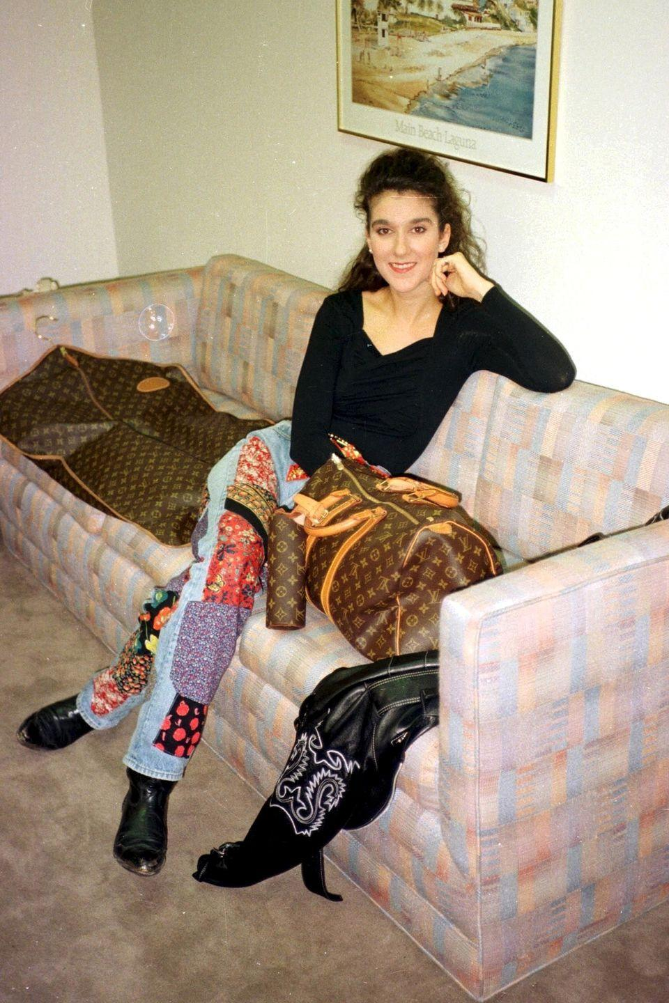 <p>A then-22-year-old Celine showed off her fashion range from the start in high-waisted patchwork jeans and black leather cowboy boots. She surrounded herself with Louis Vuitton luggage to top off the look, as one does. </p>