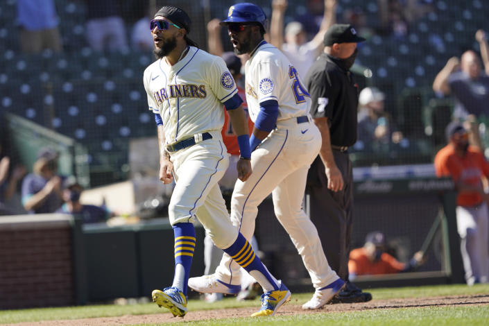 Seattle Mariners' J.P. Crawford, left, and Taylor Trammell react after they scored on a two-run triple hit by Mitch Haniger during the fifth inning of a baseball game against the Houston Astros, Sunday, April 18, 2021, in Seattle. (AP Photo/Ted S. Warren)