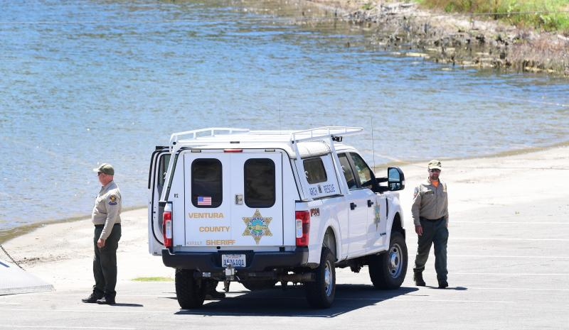 """Ventura County Sheriff's deputies stand near a vehicle near the shoreline at Lake Piru, north of Los Angeles, California, on July 13, 2020, where a body presumed to be missing """"Glee"""" actress Naya Rivera has been found. - Rescuers on July 13 found a body at the California lake where """"Glee"""" star Naya Rivera went missing last week. The Ventura County Sheriff's office said """"recovery is in progress"""" of the unidentified body, after a sixth day of searching for the US actress began again at first light. (Photo by Frederic J. BROWN / AFP) (Photo by FREDERIC J. BROWN/AFP via Getty Images)"""