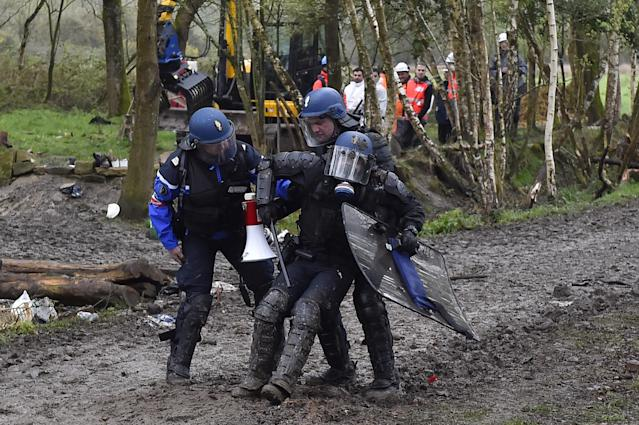 <p>An injured riot gendarme is helped by comrades when clashes erupt with protesters on April 10, 2018 during a police operation to raze the decade-old camp known as ZAD (Zone a Defendre – Zone to defend) at Notre-Dame-des-Landes, near the western city of Nantes, and evict the last of the protesters who had refused to leave despite the government agreeing to ditch a proposed airport. (Photo: Loic Venance/AFP/Getty Images) </p>