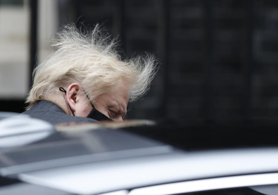 Britain's Prime Minister Boris Johnson leaves 10 Downing Street for the House of Commons for the weekly Prime Ministers Questions in London, Wednesday, Jan. 27, 2021. Britain's official death toll in the coronavirus pandemic has passed 100,000. The unwanted milestone was reached Tuesday as the government considered imposing hotel quarantines on international travelers to stop new virus variants reaching the country. (AP Photo/Alastair Grant)