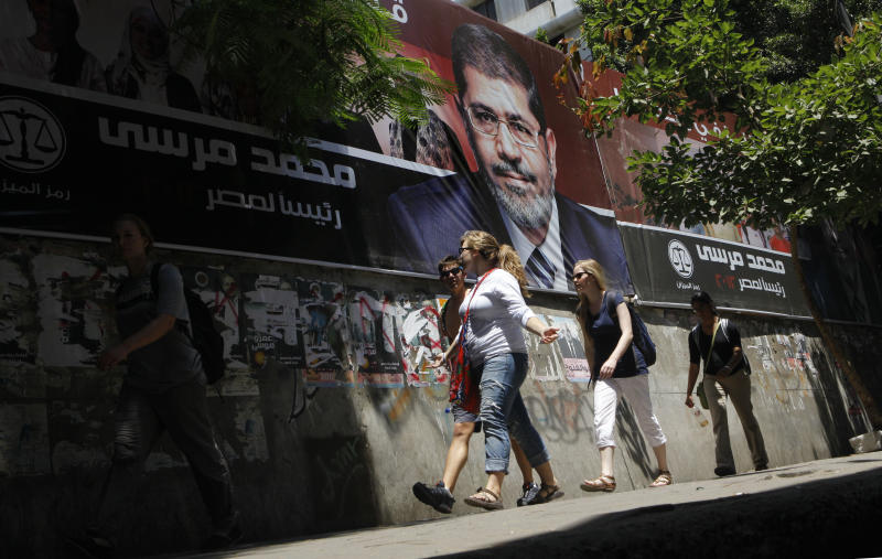 """Tourists walk past a campaign poster supporting Egyptian presidential candidate Mohammed Morsi in Cairo, Egypt, Tuesday, June 12, 2012. Arabic on the poster reads, """"Mohammed Morsi for Egyptian presidency.""""(AP Photo/Amr Nabil)"""