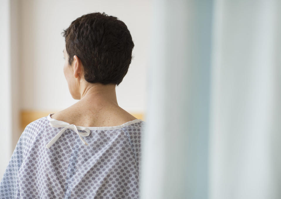 USA, New Jersey, Jersey City, Rear view of senior woman wearing hospital gown