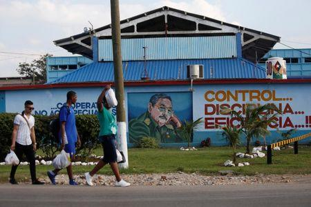 People pass by an image of Cuba's President Raul Castro in Havana, Cuba, December 21, 2017. REUTERS/Stringer/Files