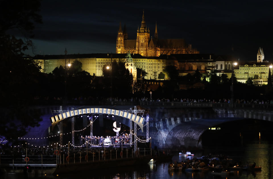 People enjoy a concert of British violinist Daniel Hope set on a floating stage on the Vltava river in Prague, Czech Republic, Saturday, Sept. 19, 2020. The Czech Republic has been been facing the second wave of infections of COVID-19. The number of new confirmed coronavirus infections has been setting new records almost on a daily basis. The Prague Castle is in the background. (AP Photo/Petr David Josek)