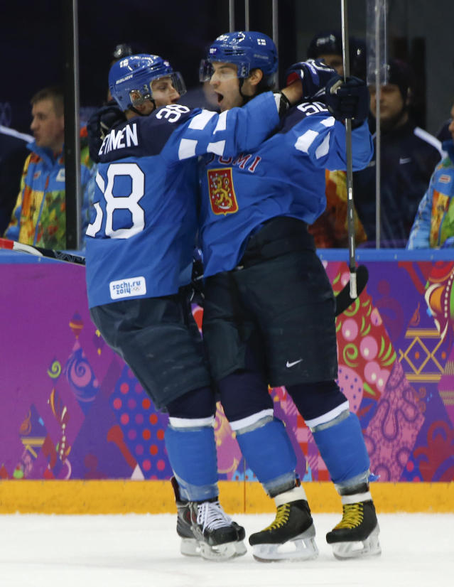 Finland defenseman Juuso Hietanen celebrates with forward Juhamatti Aaltonen after Aaltonen scored a goal against Russia in the first period of a men's quarterfinal ice hockey game at the 2014 Winter Olympics, Wednesday, Feb. 19, 2014, in Sochi, Russia. (AP Photo/Julio Cortez)