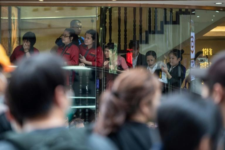 Restaurant workers and tourists looked on as protesters blocked streets (AFP Photo/Philip FONG)