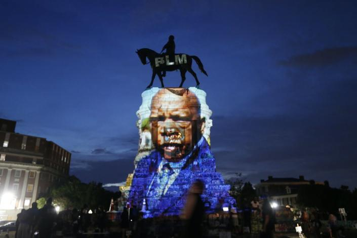 A statue of a man on horseback has a color image of a Black man projected onto its base.