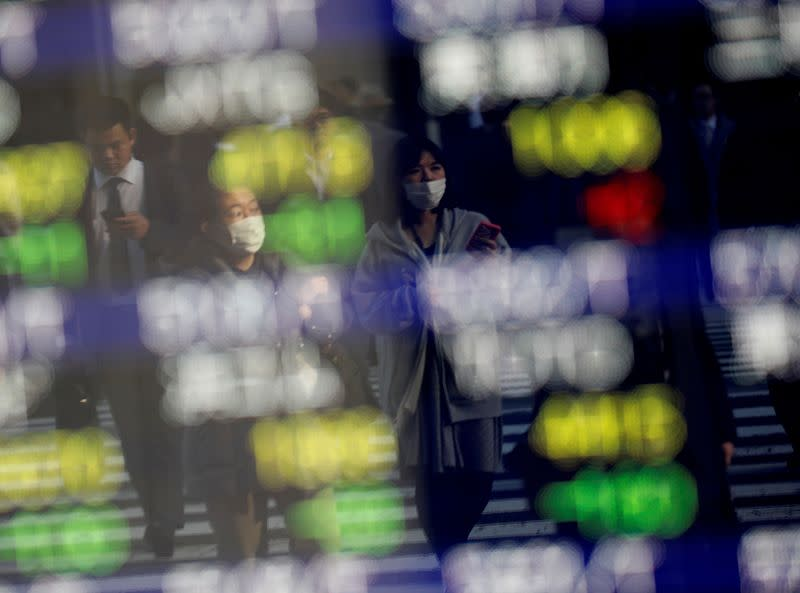 FILE PHOTO: Pedestrians wearing facial masks are reflected on an electric board showing stock prices outside a brokerage at a business district in Tokyo