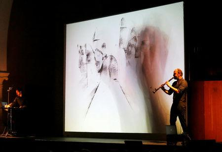 Kinan Azmeh plays the clarinet as Kevork does live sketching during their performance in Beirut, Lebanon March 26, 2018. REUTERS/Mohamed Azakir
