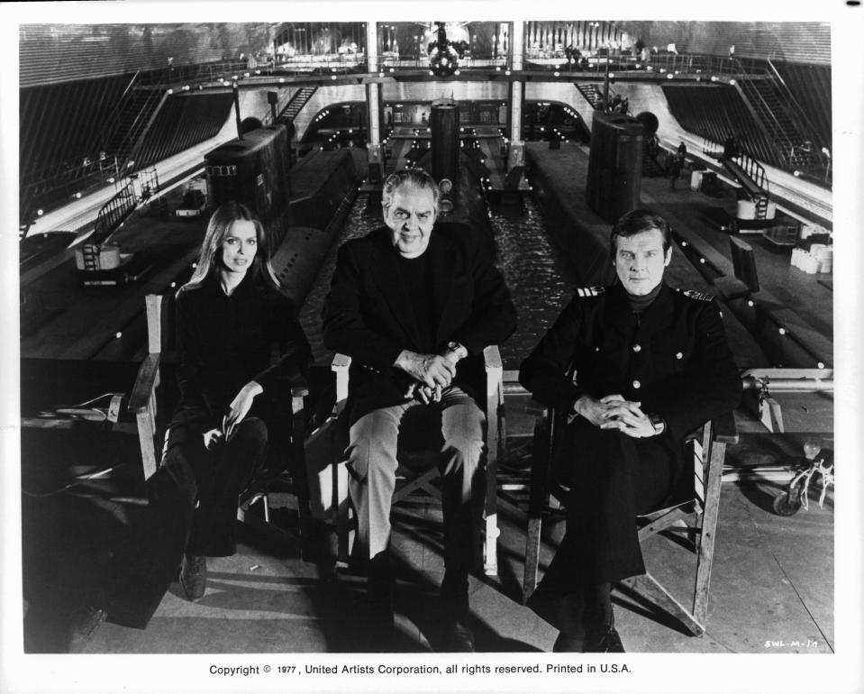 Actors Barbara Bach and Roger Moore sitting in front of a submarine tank at Pinewood Studios with producer Albert R. Broccoli between them, during the making of the James Bond film 'The Spy Who Loved Me', 1977. (Photo by United Artist/Getty Images)