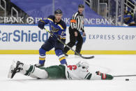 St. Louis Blues' Jaden Schwartz (17) slides the puck past a diving Minnesota Wild's Jared Spurgeon in the second period of an NHL hockey game, Wednesday, May 12, 2021 in St. Louis. (AP Photo/Tom Gannam)