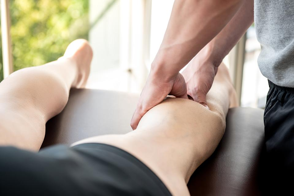 Male therapist giving leg and calf massage to a person lying on a bed.