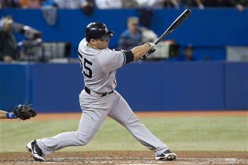 New York Yankees' Russell Martin swings on a three-run home run off Toronto Blue Jays pitcher Jason Frasor during the sixth inning of a baseball game in Toronto on Friday, Sept. 28, 2012. (AP Photo/The Canadian Press, Chris Young)