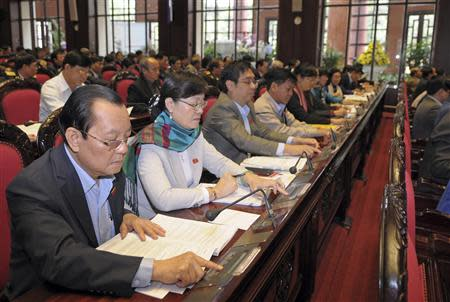 Vietnam's National Assembly's deputies press voting buttons to pass the new constitution during a meeting in Hanoi November 28, 2013. REUTERS/Stringer
