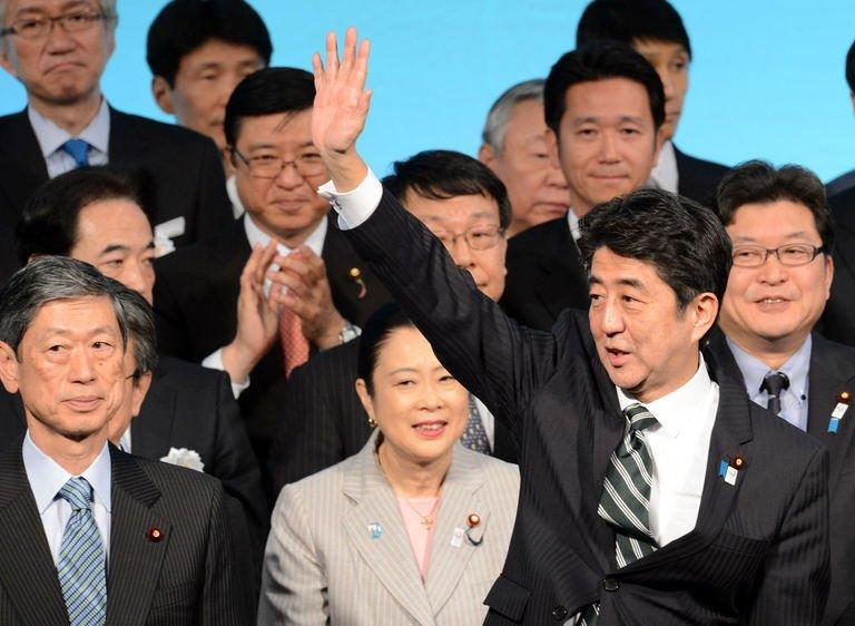 Japanese Prime Minister Shinzo Abe (R) waves at the party's annual convention in Tokyo on March 17, 2013