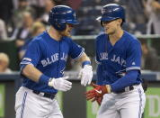 Toronto Blue Jays' Billy McKinney, left, is congratulated by teammate Cavan Biggio on his lead-off home run against the Baltimore Orioles during the first inning of a baseball game, Wednesday, Sept. 25, 2019 in Toronto, (Fred Thornhill/The Canadian Press via AP)