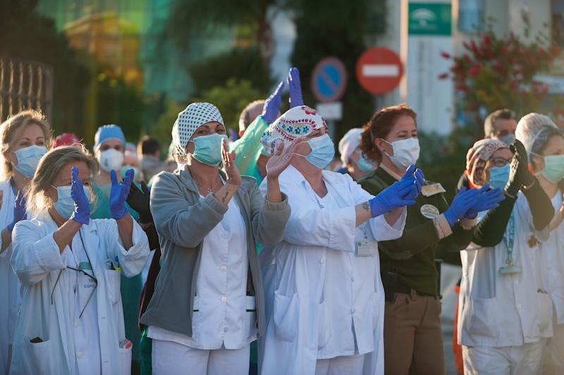 MALAGA, SPAIN - 2020/04/03: Nurses and doctors of the Regional Hospital in downtown retuning the applause (which has become a custom every evening) to those that show gratitude towards during the fight against the Covid-19 virus outbreak. Spain is the first country in Europe with more than 110.000 people infected and almost 11.000 deaths around the country, according to National Health Service sources. Andalusia is the city with more people infected by the virus. (Photo by Jesus Merida/SOPA Images/LightRocket via Getty Images)
