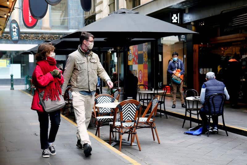 FILE PHOTO: FILE PHOTO: FILE PHOTO: People walk past a cafe after the coronavirus disease (COVID-19) restrictions were eased for the state of Victoria, in Melbourne