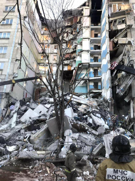 This image provided by the Russian Emergency Situations Ministry taken from tv footage, shows Emergency Situations employees working at the scene of a collapsed section of an apartment building in Magnitogorsk, a city of 400,000 about 1,400 kilometers (870 miles) southeast of Moscow, Russia, Monday, Dec. 31, 2018. Russian emergency officials say that at least four people have died after sections of an apartment building collapsed after an apparent gas explosion in the Ural Mountains region. (Chelyabinsk Region Governor Press Service photo via AP)