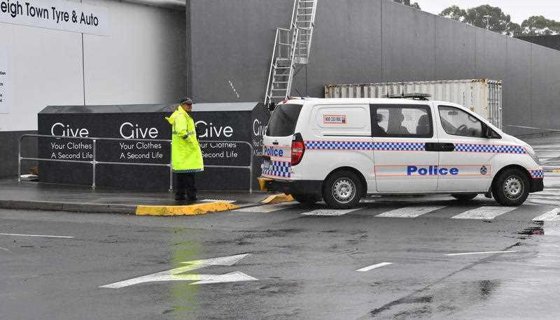 A Queensland police officer in a high-visibility jacket on next to the charity bin, with a van parked nearby.