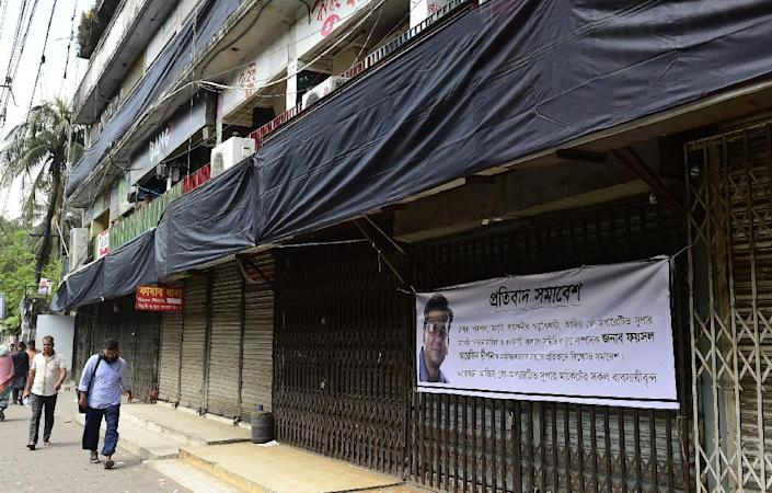 A banner bearing the image of Bangladeshi publisher Faisal Arefin Dipan, hacked to death in an attack by suspected Islamists, hangs from the front of closed shops at the Aziz Market in Dhaka's Shahbagh district on November 2, 2015 (AFP Photo/Munir Uz Zaman)