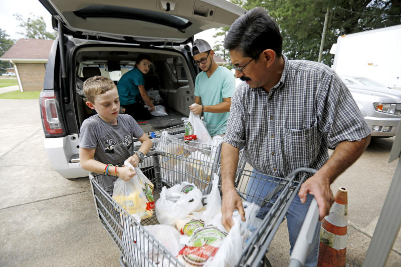 In this Thursday, Aug. 8, 2019 photo, Pastor Hugo Villegas, right, and his son Pablo Villegas, second from right, assist Cade Vowell, left, and his sister Addison Vowell, second from left, unload donated items for the pantry at the Carlisle Crisis Center in Forest, Miss. The center, a ministry of Scott County Baptist Association, says they will need more food items to help out the families affected by the fallout of Wednesday's raid by U.S. immigration officials at poultry plants Koch Foods and PH Foods in neighboring Morton. The raids were part of a large-scale operation targeting owners as well as undocumented employees. (AP Photo/Rogelio V. Solis)