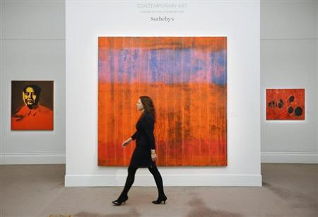 """An employee poses with artist Gerhard Richter's artwork """"Wand (Wall)"""" in between works by Andy Warhol """"Mao"""" (L) and Alberto Rossi's """"Rosso Plastica"""" (R) at Sotheby's auction house in London January 29, 2014. REUTERS/Luke MacGregor"""