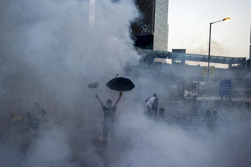 A pro-democracy demonstrator can be seen among the tear gas fired by police towards protesters near Hong Kong government headquarters on September 28, 2014 (AFP Photo/Xaume Olleros)