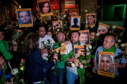 """Relatives of the victims pinned their pictures at the """"wall of truth"""", a section of the fencing around the tower featuring messages and candles"""