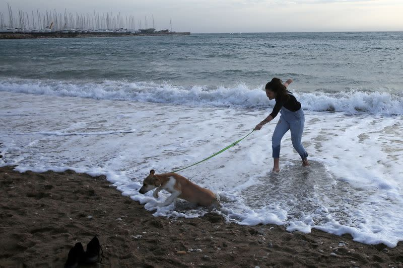 A woman plays with a dog on a beach during an unusual warm day, amid the coronavirus disease (COVID-19) pandemic, in Athens