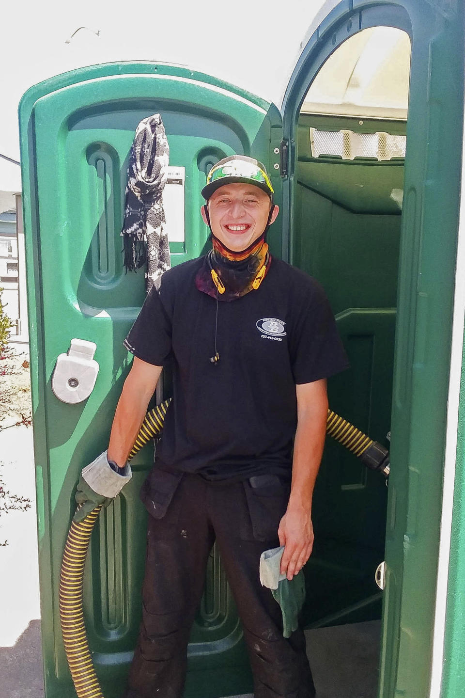 Donnie Settles, 27, stands near a portable toilet on July 14, 2020, which he services for his employer in Arcata, Calif. Settles lived at an emergency tent shelter for two months during COVID-19 while he saved up money for rent. Many homeless people work low-wage essential jobs on the front lines of the pandemic, putting them at higher risk of catching and possibly transmitting the virus. Many who work with these communities are reluctant to speak about this risk for fear of further stigmatizing homeless people, even though they do the front-line jobs others can avoid. (Robert Peach/Arcata House Partnership and the Howard Center For Investigative Journalism via AP)
