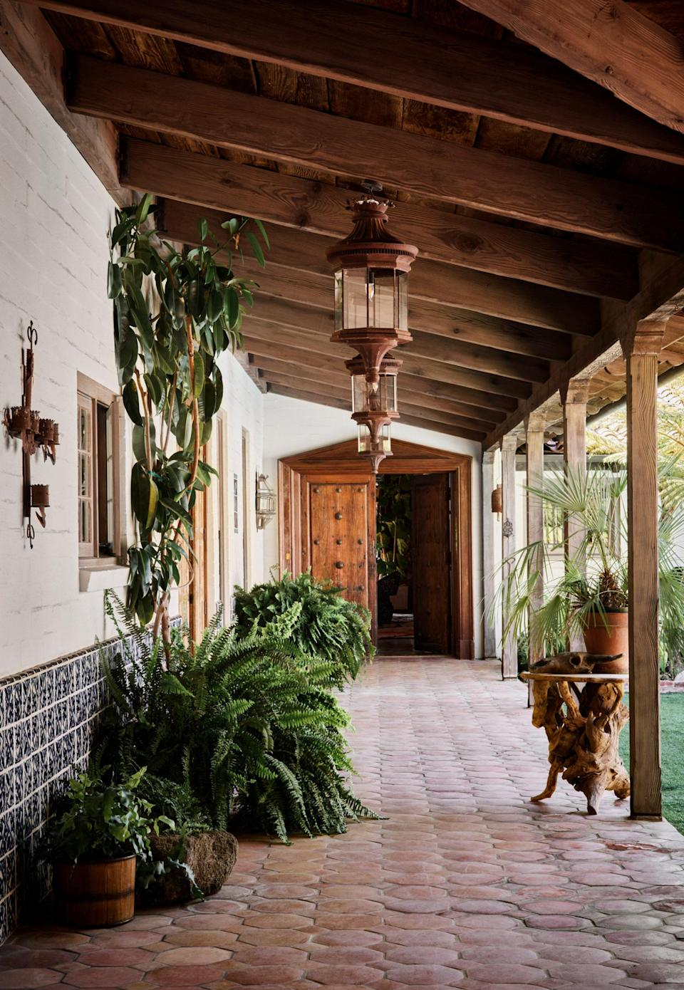 Saltillo tile floors extend from the exterior of the home to the interior. The pool is situated in the courtyard to the right.