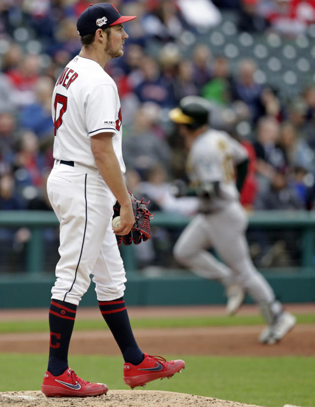 Cleveland Indians starting pitcher Trevor Bauer, left, waits for Oakland Athletics' Mark Canha to run the bases after Canha hit a two-run home run in the third inning of a baseball game, Tuesday, May 21, 2019, in Cleveland. Matt Olson scored on the play. (AP Photo/Tony Dejak)