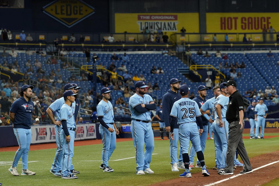Toronto Blue Jays players and coach stand on the field after Blue Jays pitcher Ryan Borucki hit Tampa Bay Rays' Kevin Kiermaier with a pitch during the eighth inning of a baseball game Wednesday, Sept. 22, 2021, in St. Petersburg, Fla. (AP Photo/Chris O'Meara)