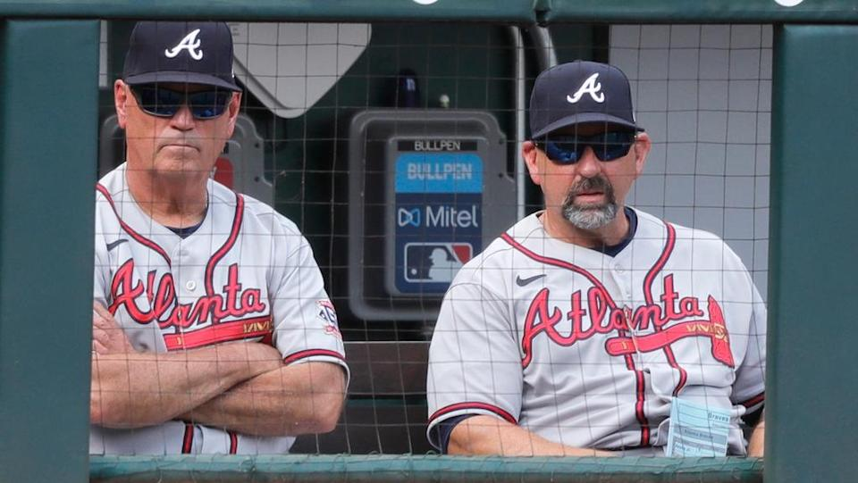 Jun 26, 2021; Cincinnati, Ohio, USA; Atlanta Braves manager Brian Snitker (left) and bench coach Walt Weiss (right) watch from the dugout during a game with the Cincinnati Reds at Great American Ball Park.