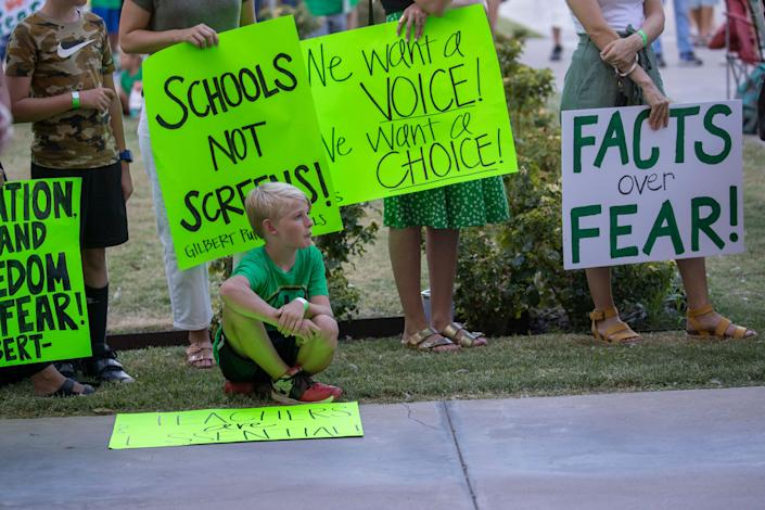 """Grayson Bair, 9, from Highland Park Elementary in Gilbert, Ariz., attends  the """"AZ Open Our Schools Rally"""" with his family at the state Capitol In Phoenix."""