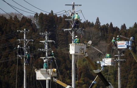 Workers climb poles to fix power lines in Minamisanriku, Miyagi prefecture, after the area was devastated by the March 11 magnitude 9.0 earthquake and tsunami, in this April 6, 2011 file photo. REUTERS/Toru Hanai/Files