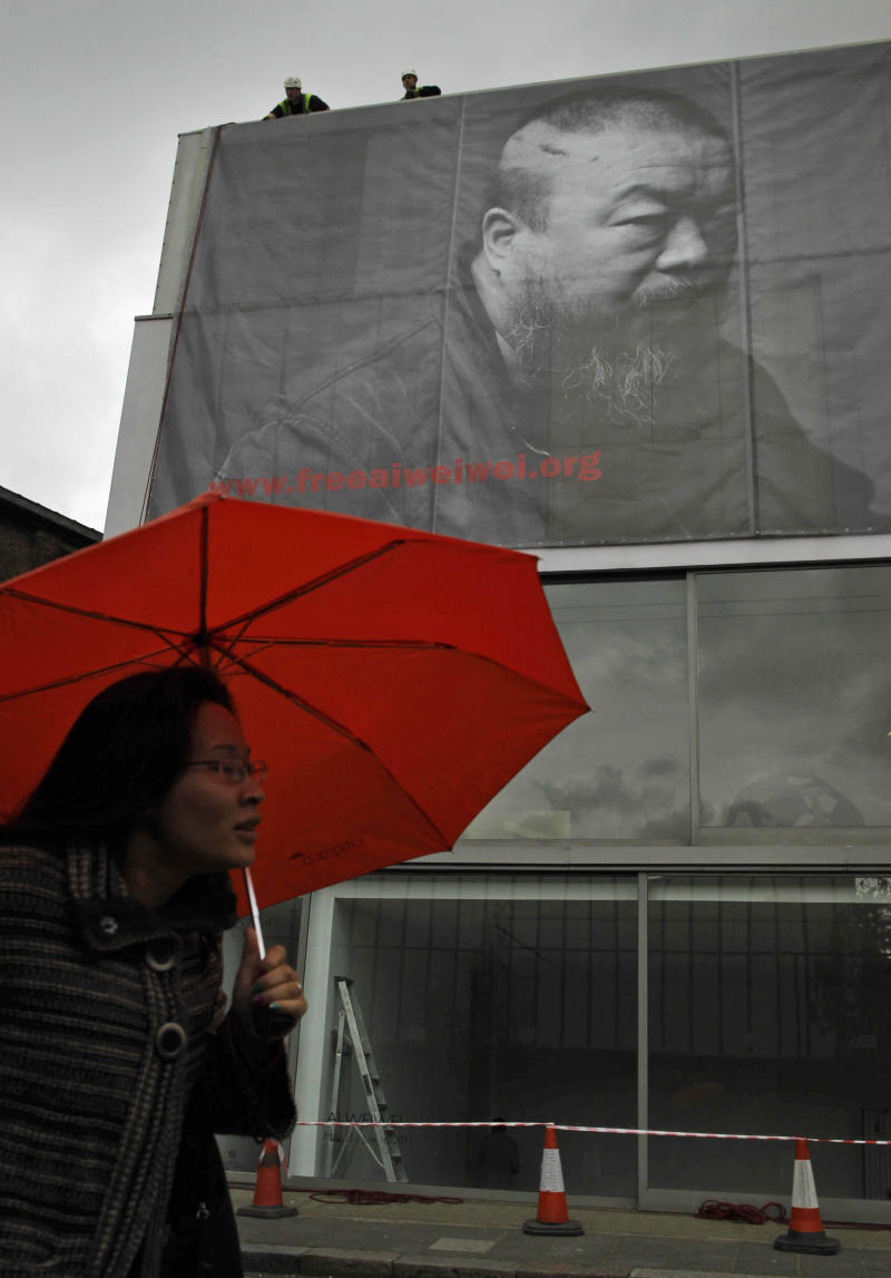 A woman sheltering under an umbrella from the rain walks past as workers put up a two-story-high black-and-white photograph of Chinese artist Ai Weiwei outside the Lisson Gallery in London, Wednesday, May 11, 2011.  Chinese artist Ai Weiwei has vanished. But look around, and he seems to be everywhere.  More than a month after one of China's best-known contemporary artist was arrested while trying to board a flight to Hong Kong, his name, his face and his art have been popped up across the globe. China's communist rulers have steadfastly refused to say where Ai is or who's holding him. His colleagues in the international art world say they want to make sure he doesn't disappear from view.  (AP Photo/Matt Dunham)