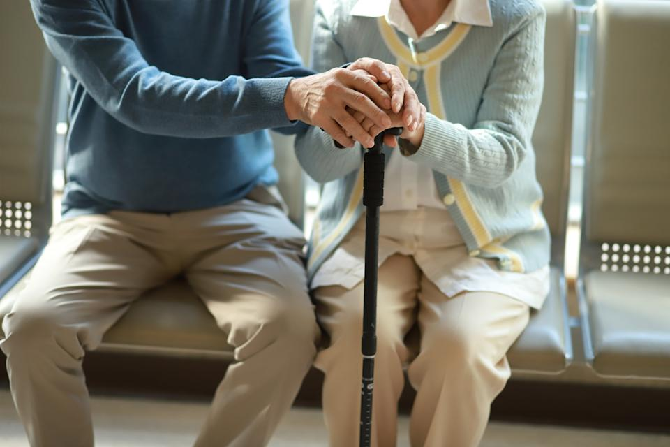 Senior couple holding hands with walking cane